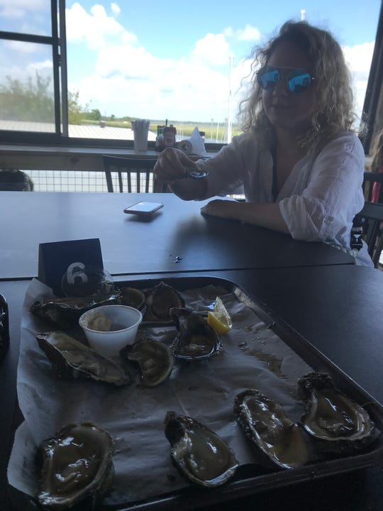 Alina Fooks, a visiting journalist from Moscow in the International Center for Journalists program, enjoys oysters on the half shell at Up the Creek Raw Bar in Apalachicola.