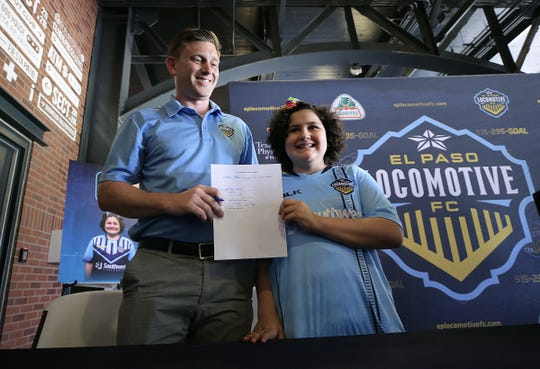 El Paso Locomotive FC General Manager Andrew Forrest holds a one-day contract signed by Amber Berry, 11, on Friday, June 21, 2019, at Southwest University Park.