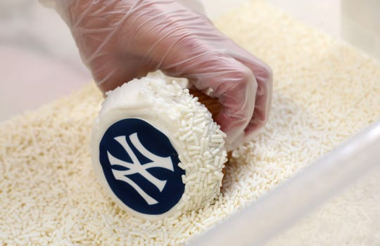 Designer/decorator Marisa O'Connor sprinkles a cupcake for the Yankees Old-Timers party at Homestyle Desserts Bakery in Peekskill June 21, 2019. The bakery has been making the cakes for the Old Timers Game celebration for the past decade.