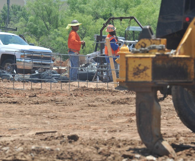 Construction workers extend Maplewood Avenue into Mcniel Avenue, Thurday afternoon.