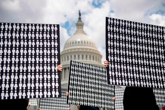 Demonstrators hold up placards representing the number of the people who have died because of gun violence on Capitol Hill on June 20, 2019, during an event with gun violence prevention advocates.