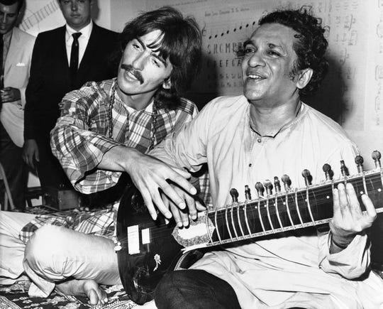 George Harrison (left) sits beside his Indian music mentor Ravi Shankar, who taught the Beatle how to play sitar in 1967.