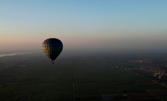 Tourists ride a hot air balloon before sunrise in Luxor, Egypt Nov. 23, 2012.