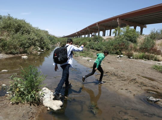 In this June 7, 2019, file photo, people cross the Rio Grande into the United States to turn themselves over to authorities and ask for asylum, as seen from Ciudad Juarez, Chihuahua, Mexico, opposite El Paso, Texas.