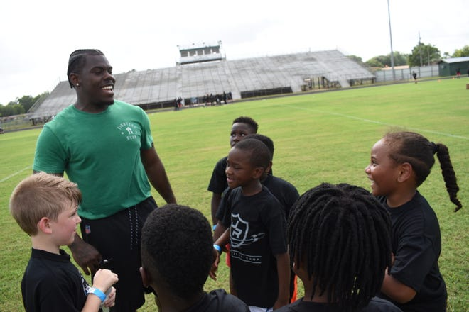 Oakland Raiders running back and former Peabody Magnet High School football player Jalen Richard (left) shares a few laughs with campers during his second annual football camp at W.C. Davis Memorial Stadium Saturday, June 22, 2019.
