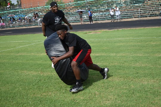 A young camper practices his tackling form on a tackle wheel at Jalen Richard's second annual football camp at W.C. Davis Memorial Stadium Saturday, June 22.