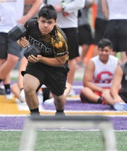 A Snyder athlete competes in the four-way dumbell stack at the State LineMAN Challenge on Saturday, June 22, 2019, at Hardin-Simmons' Shelton Stadium. One teammate would race against the clock to put four dumbells on four different stands, while another had to take them down in the five-man total relay event.