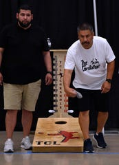 Jesse Adame of Dallas (left) watches as John Lopez of Grand Prairie throws his bag during Friday's Cornhole games at the Abilene Convention Center. This was the ninth state competition for the league.