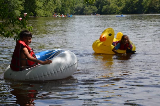 Nine-year-old twins Orion Simmons and Adrianna Simmons float down the Kalamazoo River as part of the Raft Race hosted by the Battle Creek Metropolitan Area Moustache Society on Saturday, June 22, 2019.