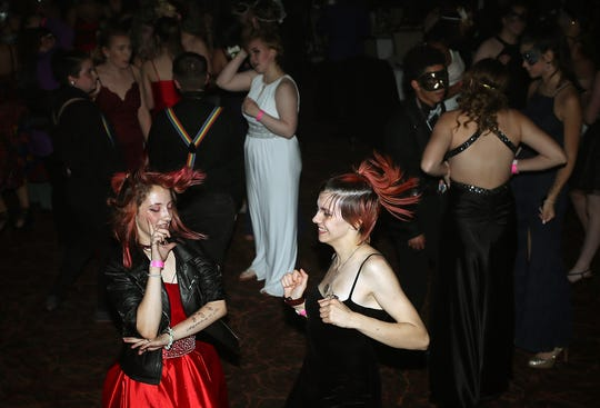 "Alex Rickett, 15, left, and Dani Mathews, 16, dance during the Pink Prom. The theme for the event was ""Mas-Queer-Ade,"" and students danced the night away to a DJ, drag shows and feasted on a buffet."