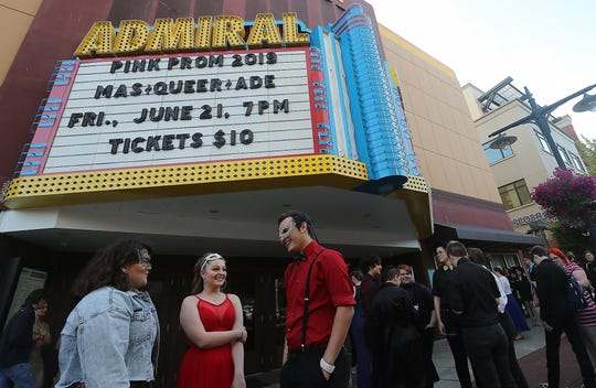 Friends, left to right, Katrina Jones-Morales, 19, Kenna Grunden, 19, and Tristan Beller, 19, chat underneath the marquee as they wait for the doors to open for Pink Prom at the Admiral Theatre on Friday. The prom is sponsored by the Q Center and a place where LGBTQ youth can bring the date of their choice in a welcoming environment.
