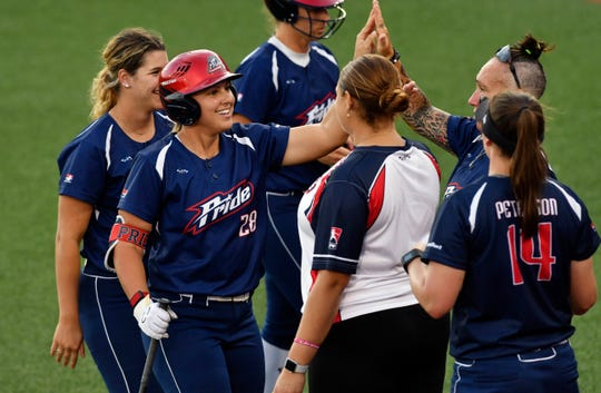 Amanda Lorenz (28) of the USSSA Pride is high fives by teammates after her home run in Friday's game against the Aussie Peppers.