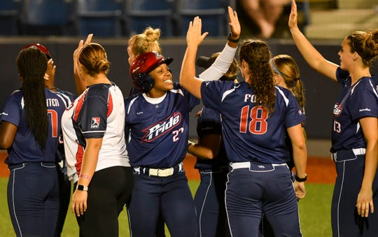 The USSSA Pride celebrate a 7-0 victory against the Aussie Peppers.