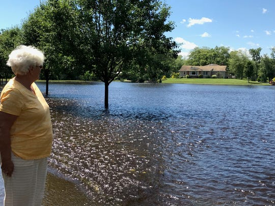 Joanne Ferrell gazes at her Lumberton home surrounded by flood waters that prevented her from returning Thursday and Friday following torrential storms