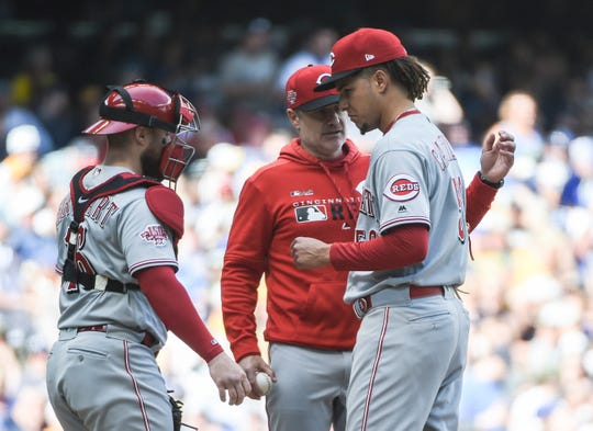 Jun 22, 2019; Milwaukee, WI, USA;  Cincinnati Reds pitcher Luis Castillo (58) is visited at the mound by manager David Bell and catcher Tucker Barnhart (16) during a pitching change in the fourth inning during the game against the Milwaukee Brewers at Miller Park. Mandatory Credit: Benny Sieu-USA TODAY Sports