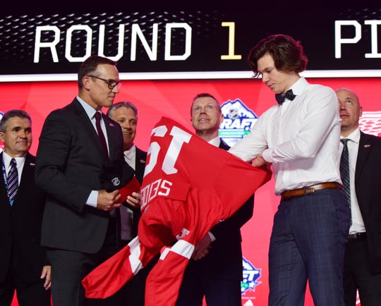 Detroit Red Wings GM Steve Yzerman watches, as Moritz Seider puts on a jersey after being selected sixth overall in the first round of the NHL draft at Rogers Arena, June 21, 2019 in Vancouver.
