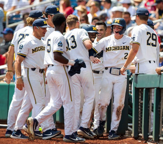 Michigan's Jack Blomgren (2) is greeted after scoring against Texas Tech during an NCAA College World Series baseball game Friday, June 21, 2019, in Omaha, Neb.