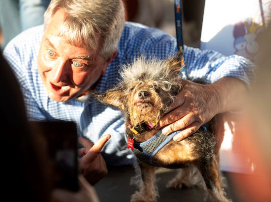 Scamp the Tramp celebrates after taking top honors in the World's Ugliest Dog Contest at the Sonoma-Marin Fair in Petaluma, Calif., Friday. At left is Kerry Sanders, one of the judges.