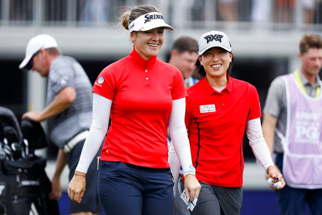 Hannah Green, of Australia, walks off the 18th green with Jennifer Song, right, after finishing their second round Friday of the KPMG Women's PGA Championship golf tournament. She took a three-shot lead after a 3-under 69.