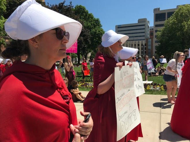 "Dressed in a red cloak and white bonnet to represent oppressed female characters in Margaret Atwood's ""The Handmaid's Tale,"" Carrie Gallup listens to speakers on the Capitol lawn Saturday, June 22, 2019 during a rally opposing bans that would limit legal abortion procedures in Michigan."