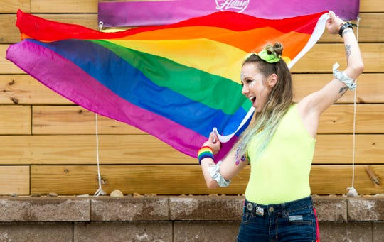 Maddy Liles waves the Rainbow flag on the patio of Mo's House during the River City Pride Festival Saturday, June 22, 2019.