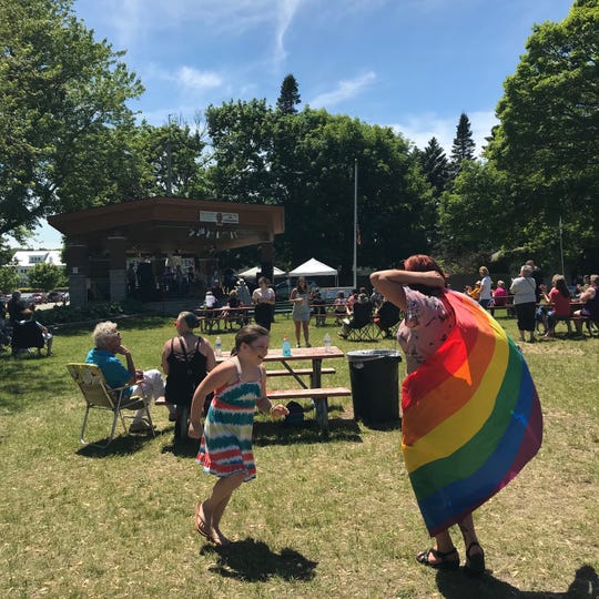 Open Door Pride Festival attendees dance with rainbow flags during one of several musical performances on Saturday, June 22, 2019, in Sturgeon Bay, Wis.