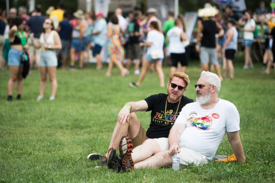 From left, Jeff Jarnigan and Brent Collins sit on the lawn at the Civic Coliseum at Knoxville Pridefest, Saturday, June 22, 2019.