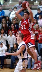 Plymouth's Mike LaCroix makes a pass over Mitchell Fogg's head in 2006 in the Division IV boys district tournament at Willard High School.  Plymouth won 60-53.
