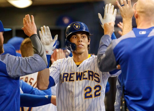 Brewers rightfielder Christian Yelich is greeted in the dugout after his 29th home run.