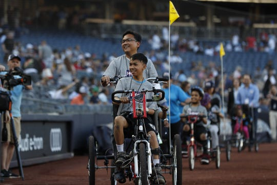 Kiko Mina, a 14-year-old from Jefferson, and his father, Joseph, pedal an AdaptAbility bicycle around the warning track at Yankee Stadium before the game on June 21.