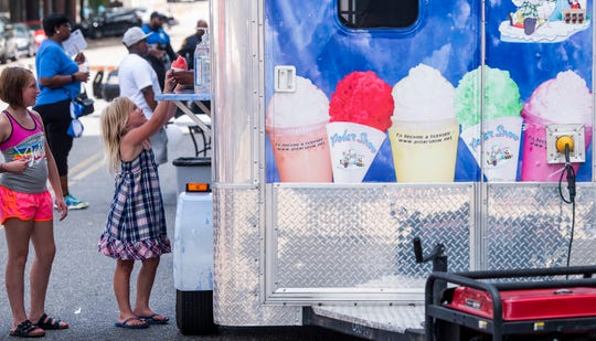 Meleaha Becerra, left, and Olivia Kennedy get a cold treat as the annual Juneteenth Celebration is held in front of the Rosa Parks Museum in Montgomery, Ala., on Saturday June 22, 2019.