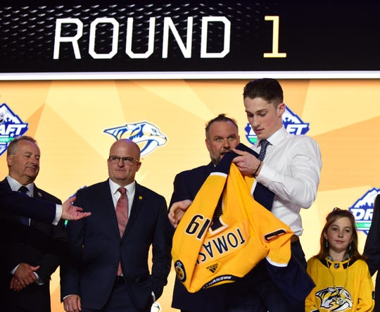 Philip Tomasino puts on a jersey after being selected as the No. 24 overall pick to the Nashville Predators in the first round of the 2019 NHL Draft in Vancouver on June 21, 2019.