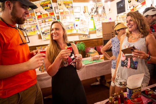 """Dianne Lawson, right, laughs as she watches Andrew Petro, left, and Emily Petro, center, take a shot of Jessi Hamlin's """"Spam Over Special"""" Bloody Mary during the annual Spammy Jammy party at the Little Bar in Goodland on Saturday, June 22, 2019."""