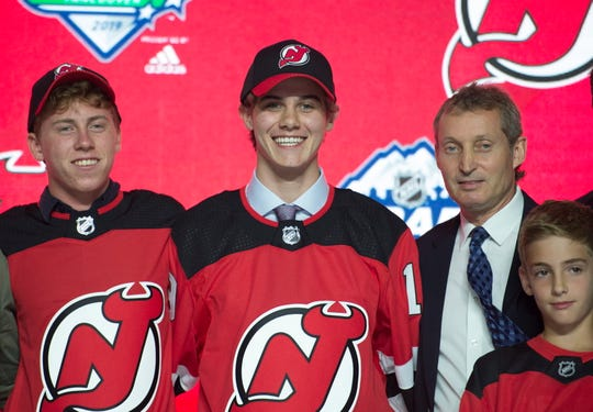 Jack Hughes, center, poses for photos after being selected by the New Jersey Devils with the first pick in the NHL hockey draft in Vancouver, British Columbia, Friday, June, 21, 2019.