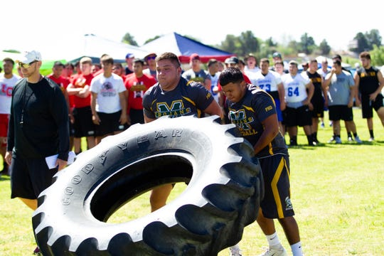 Mayfield High School teammates (L), Juan Castillo, 16, and Omar Munoz, 17 participate in the tire flip. Doug Martin's Football Camp was held at New Mexico State University over the weekend.