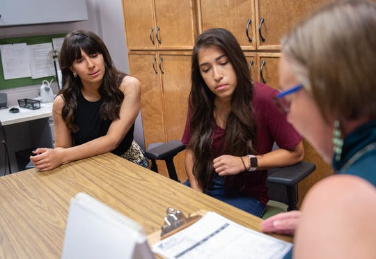 Heike Lehnert-LeHoillier a professor in the New Mexico State University Communications Sciences Department, speaks with two of her students Celinda Acosta, center and Laura Benitez, left,  who are helping run a research program about autism.