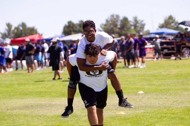 Oñate's Neo Quinones, 17, is carried by Isaiah Ibarra, 15, in the fireman carry. The were participating in Doug Martin's Football Camp held at New Mexico State University on Saturday.