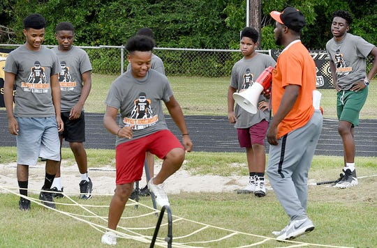 Campers engage in agility drills at the start of Devery Henderson Skills and Drills Football Camp Saturday at Opelousas High School.
