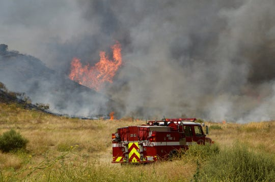 Fire personnel battle the Jerry Fire Friday near Moreno Valley.