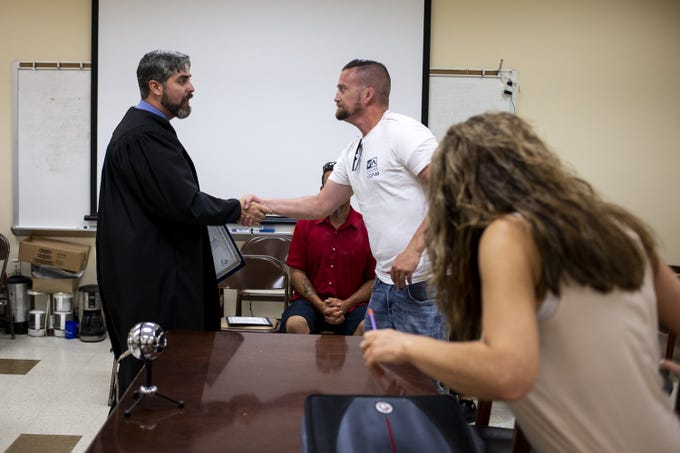 Jason Swenson shakes hands with Judge Tyler Kissell of University Lakes Justice Court during Maricopa County Homeless Court on June 18, 2019, at the Human Services Campus in Phoenix.