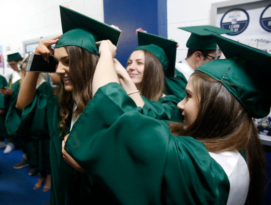 From left, Sedona Petagine gets help with her mortar board from Dominique Hollister and Bella Cupano prior to the start of the Spackenkill High School graduation while inside the McCann Ice Arena in the City of Poughkeepsie on Friday. A class of 124 graduated from Spackenkill.