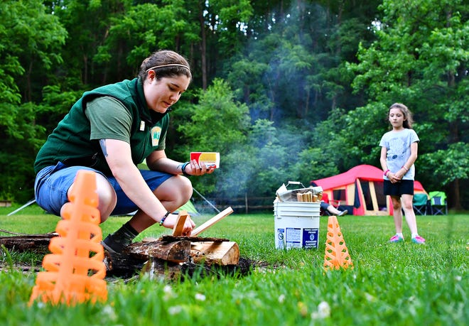 Rachel Albright, of Nixon County Park, starts a fire during the Summer Solstice Campout at Nixon County Park in Springfield Township, Friday, June 21, 2019. Dawn J. Sagert photo
