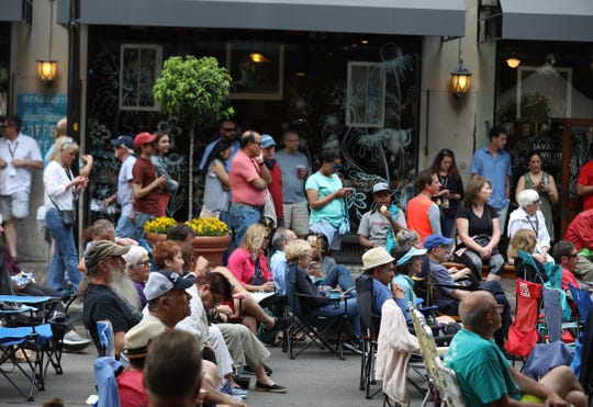 People line Gibbs St. and listen to Eastman Youth Jazz Orchestra play on the Jazz Street Stage.