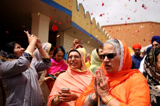 A woman prays as flower petals fall on the crowd during the Sikh Day Parade beginning at the Dasmesh Darbar Sikh Temple in Salem on June 22, 2019.