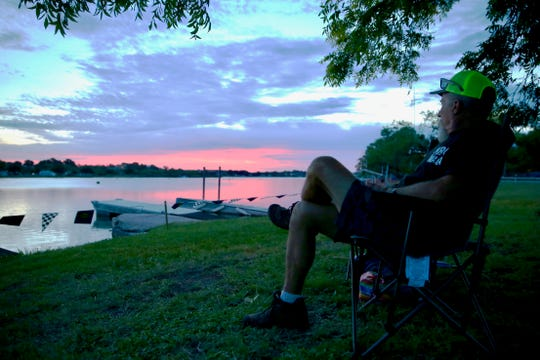 Charlie Lovelace watches the sun rise as he waits for the drag boat races to start at Lake Nasworthy on Saturday, June 22, 2019.
