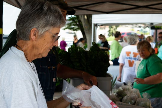 Sue Randall bags a customer's purchase on Saturday at the Staunton Farmers Market. The Randalls run Elk Run Farm in Fort Defiance.