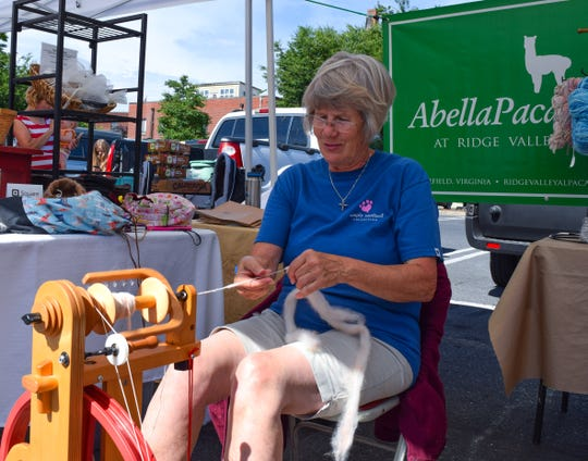 Janis Conlon demonstrates how to spin alpaca fiber on Saturday at the Staunton Farmers Market. Conlon and her husband run Ridge Valley Alpacas in Fairfield. Conlon said this is their second season at the Staunton Farmers Market.