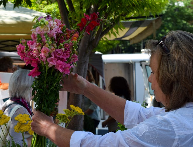 Susan Roepke removes flowers from a vase for a customer on Saturday at the Staunton Farmers Market. She said she's been a vendor at the market for 18 years.