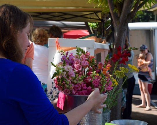 Annie Bellinger holds a vase of flowers on Saturday at the Staunton Farmers Market. Bellinger bought flowers from Susan Roepke's Flower Fields stand because Bellinger's family was preparing to host a masquerade ball.