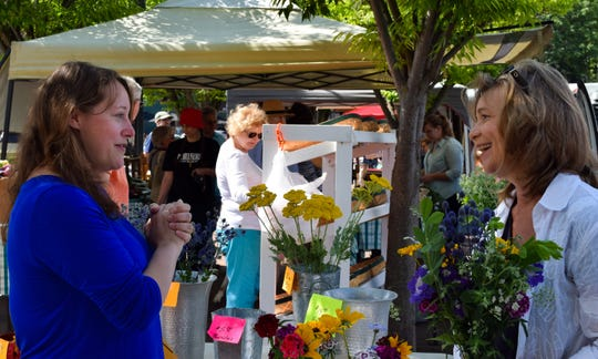 "Annie Bellinger (left) tells Susan Roepke that she wants to buy flowers for an event she's hosting. ""We're having a masquerade ball at my house,"" Bellinger explained. Bellinger said her husband works for the American Shakespeare Center, and they invited 50 people of all ages over to their house for the party."